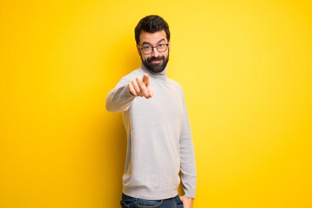 Homem com barba e gola alta aponta o dedo para você com uma expressão confiante Foto Premium