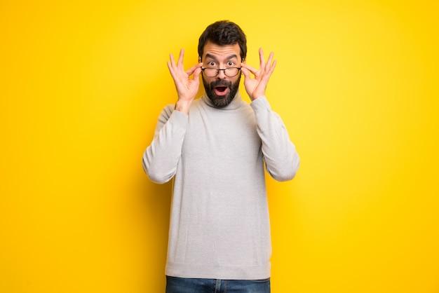 Homem com barba e gola alta com óculos e surpreso Foto Premium