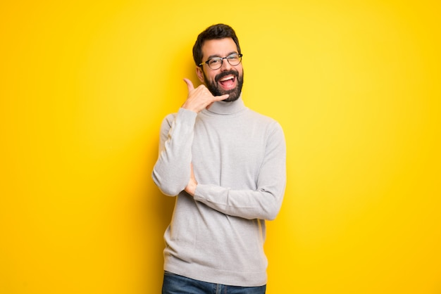 Homem com barba e gola alta fazendo gesto de telefone. me ligue de volta Foto Premium