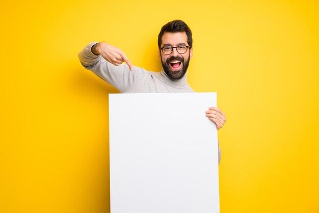 Homem com barba e gola alta segurando um cartaz branco vazio Foto Premium