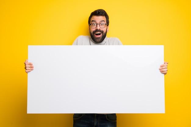Homem com barba e gola alta segurando um cartaz para inserir um conceito Foto Premium