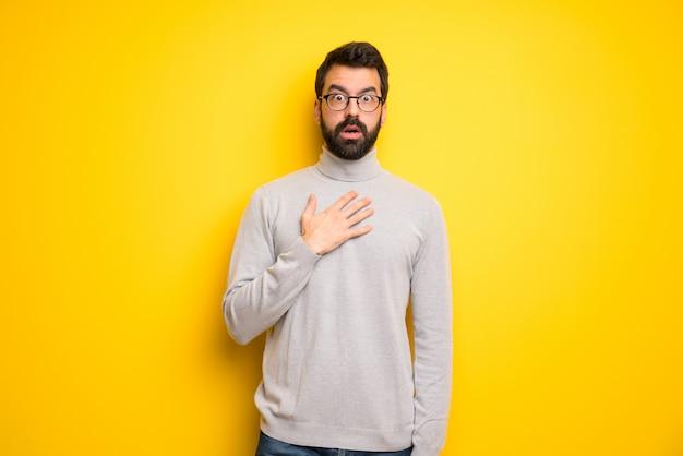 Homem com barba e gola alta surpreso e chocado ao olhar para a direita Foto Premium