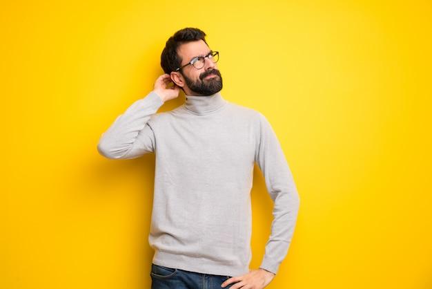 Homem com barba e gola alta tendo dúvidas enquanto coçando a cabeça Foto Premium
