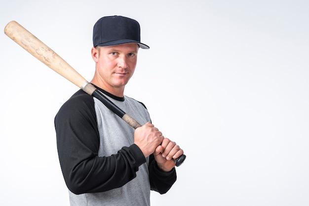 Homem com boné posando com taco de beisebol Foto gratuita