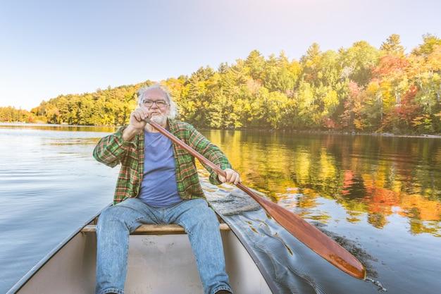 Homem com canoa no lago em um dia ensolarado de outono Foto Premium
