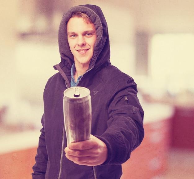 Homem com capa do hoodie put on segurando uma lata Foto gratuita