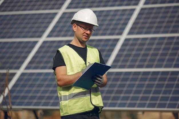 Homem com capacete branco perto de um painel solar Foto gratuita