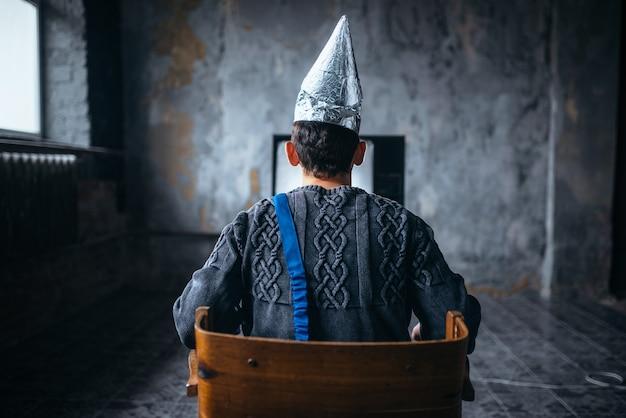 Homem com capacete de papel alumínio assiste tv, vista traseira. conceito de paranóia, ovni, teoria da conspiração, proteção contra roubo de cérebro, fobia Foto Premium