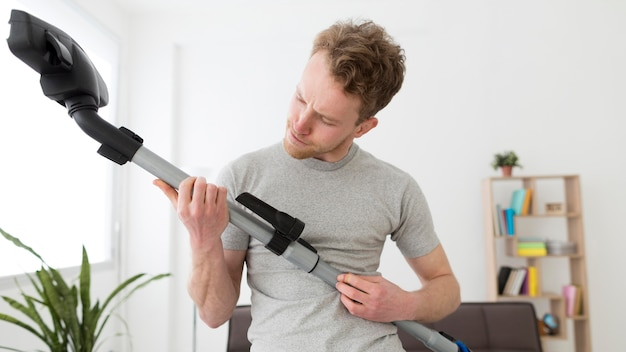 Homem com casa de limpeza a vácuo Foto gratuita