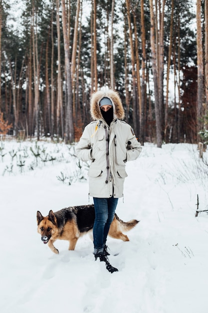 Homem com casaco de inverno na floresta com cão pastor Foto gratuita