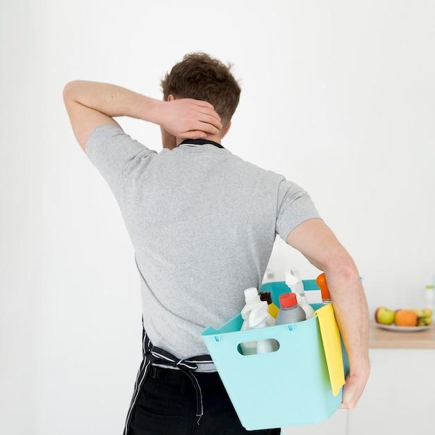 Homem com cesta de produtos de limpeza Foto gratuita