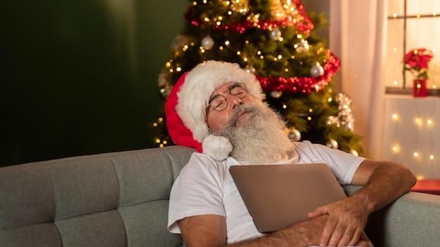 Homem com chapéu de papai noel dormindo em casa enquanto segura seu laptop Foto gratuita