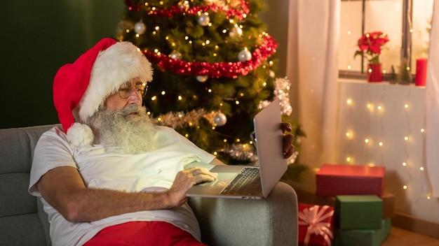Homem com chapéu de papai noel usando laptop no sofá em casa Foto Premium