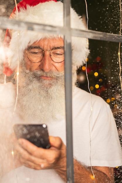 Homem com chapéu de papai noel usando smartphone pela janela Foto gratuita