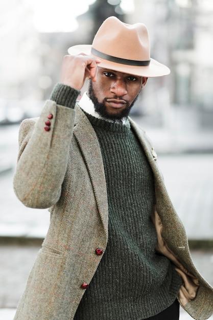 Homem com chapéu posando ao ar livre Foto gratuita