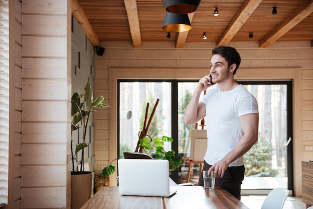 Homem com copo de água falando no telefone Foto Premium