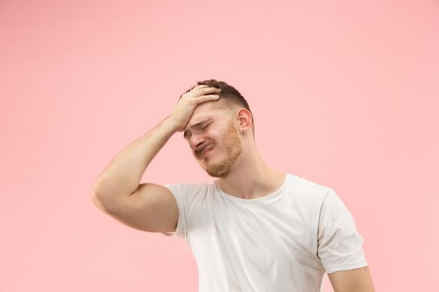 Homem com dor de cabeça. isolado sobre o fundo rosa. Foto gratuita