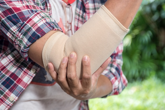 Homem com dor no cotovelo. conceito de alívio da dor Foto Premium
