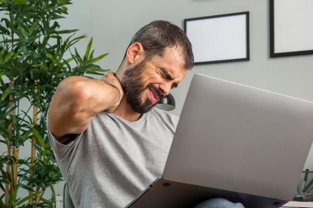 Homem com dor no pescoço enquanto trabalha em casa usando um laptop Foto gratuita