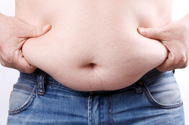 Homem com excesso de peso mantém suas dobras de gordura Foto Premium