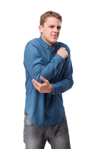 Homem com face da dor tocar seu cotovelo Foto gratuita