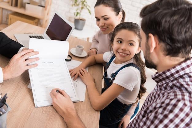 Homem com família assina contrato de vendas com corretor de imóveis confiante Foto Premium