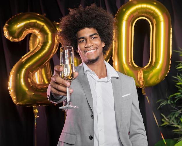 Homem com feliz ano novo 2020 balões e taça de champanhe Foto gratuita