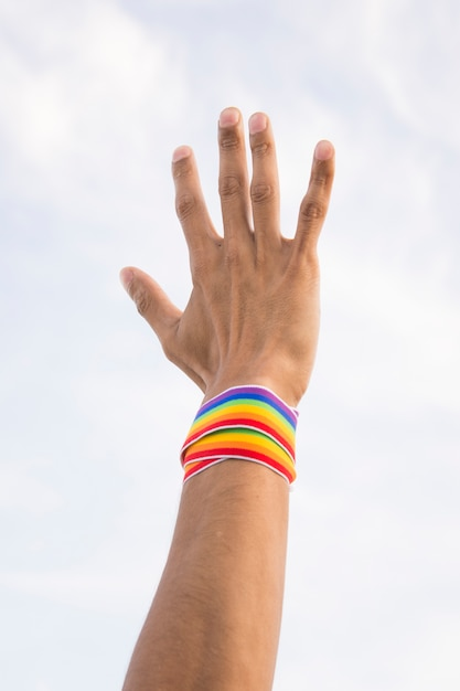 Homem com fita em cores lgbt na mão e céu azul Foto gratuita