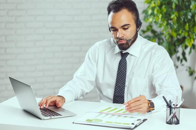 Homem com fones de ouvido. operador de call center falando com o cliente Foto Premium