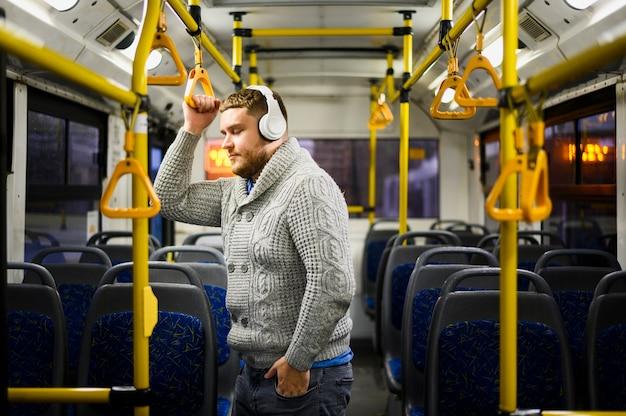 Homem com fones de ouvido, passando por transportes públicos Foto gratuita