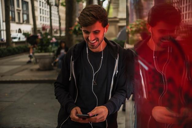 Homem com fones de ouvido sorrindo enquanto olha para smartphone Foto gratuita
