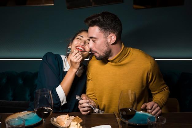 Homem, com, garfo, em, boca, perto, alegre, mulher, em, tabela, com, óculos vinho, e, alimento, em, restaurante Foto gratuita