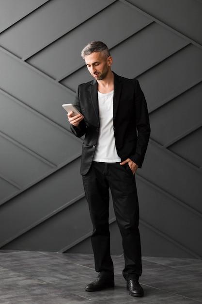Homem com jaqueta preta de pé e usando seu telefone Foto gratuita