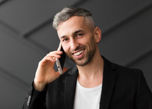 Homem com jaqueta preta fala ao telefone e sorri Foto gratuita