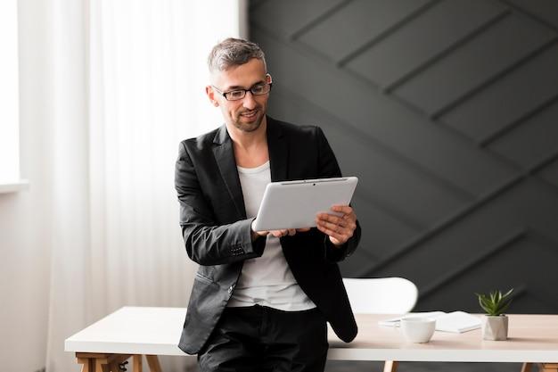 Homem com jaqueta preta, olhando para tablet Foto gratuita