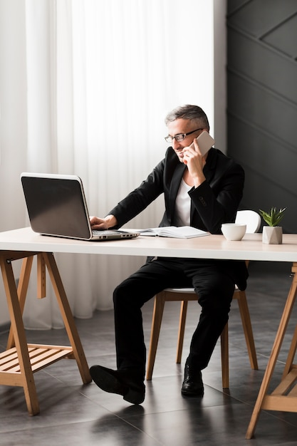 Homem com jaqueta preta, sentado a mesa Foto gratuita