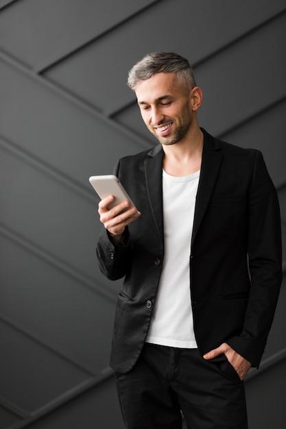 Homem com jaqueta preta, sorrindo para o seu telefone móvel Foto gratuita