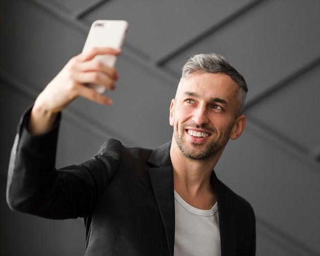 Homem com jaqueta preta tomando uma selfie Foto gratuita