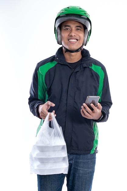 Homem com jaqueta uniforme e capacete entregando comida Foto Premium