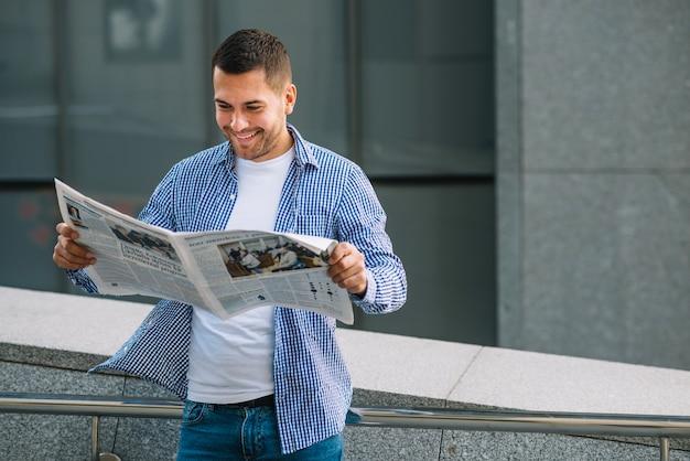 Homem com jornal apoiado no corrimão Foto gratuita