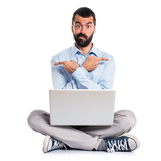 Homem com laptop apontando para as laterais com dúvidas Foto gratuita