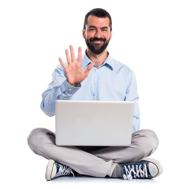 Homem com laptop contando cinco Foto gratuita