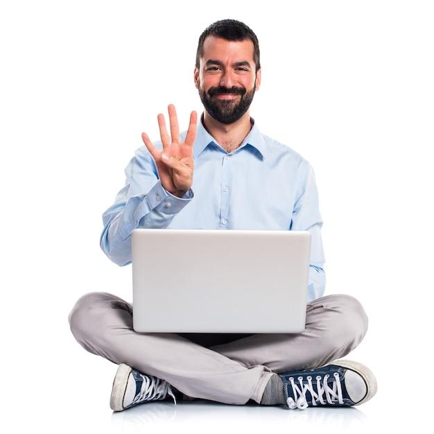 Homem com laptop contando quatro Foto gratuita