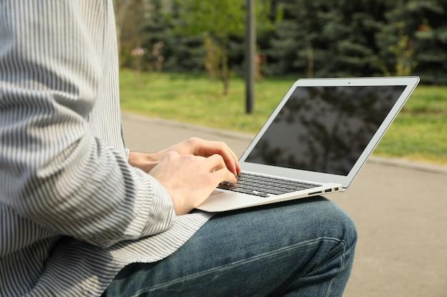 Homem com laptop trabalha no parque. trabalho ao ar livre Foto Premium