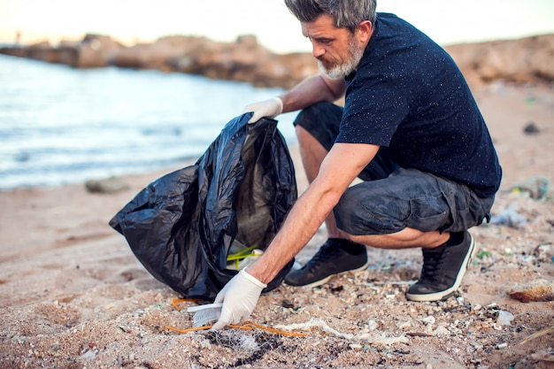 Homem com luvas brancas e um grande pacote preto coletando lixo na praia. proteção ambiental e conceito de poluição do planeta Foto Premium