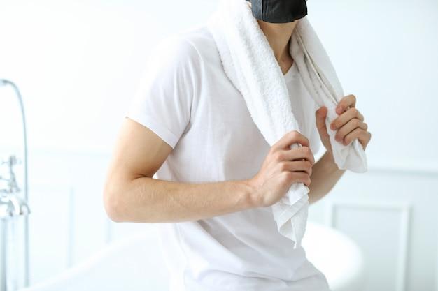 Homem com máscara facial preta, carvão purificador de pele. conceito de beleza Foto gratuita