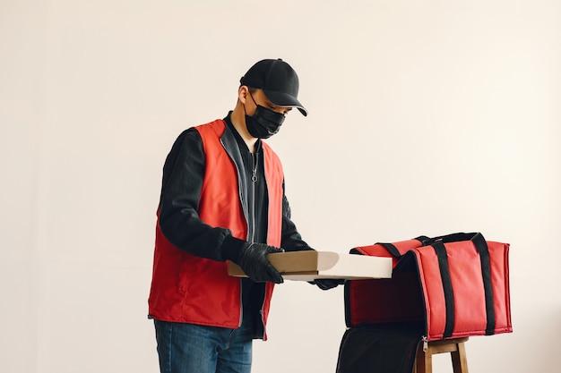 Homem com máscara médica cirúrgica de uniforme segurando caixas Foto gratuita