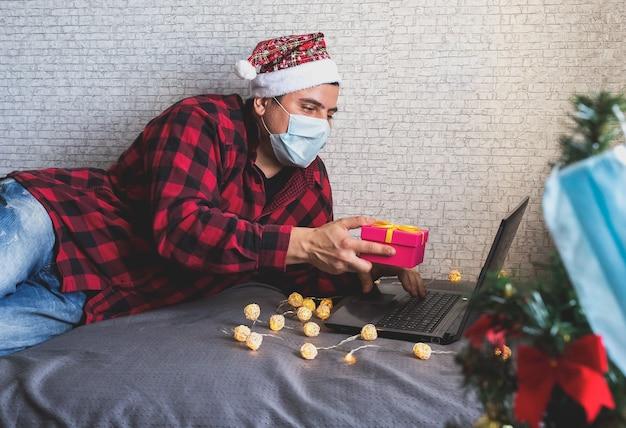 Homem com máscara médica compartilhando presentes de caixa por meio de videochamadas Foto Premium