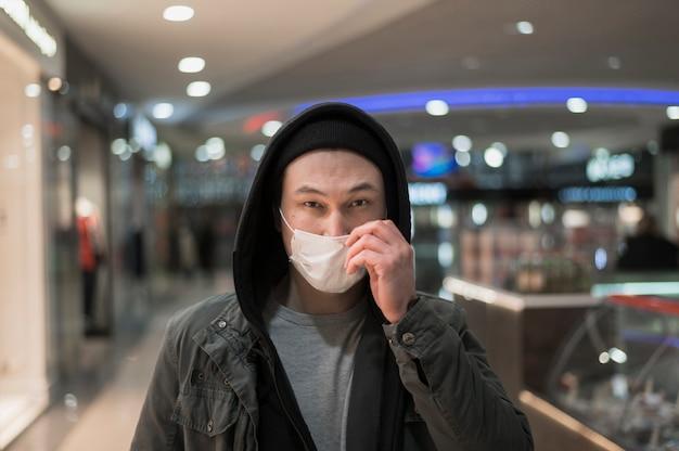 Homem com máscara médica no shopping Foto gratuita