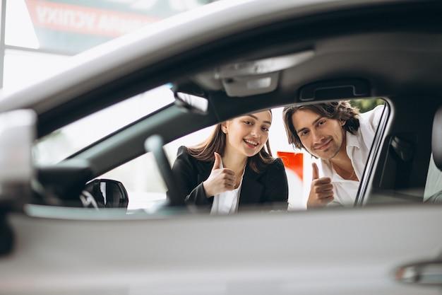 Homem com mulher escolhendo um carro em uma sala de exposições Foto gratuita